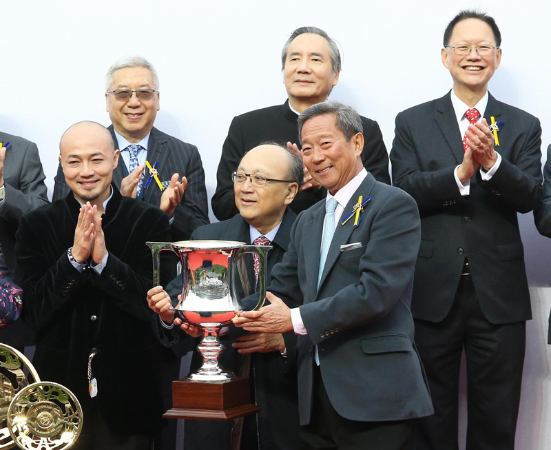 At the presentation ceremony, Club Chairman Dr Simon Ip (right) presents the Stewards' Cup trophy and gold-plated dishes to Paul Lo Chung Wai, owner of Seasons Bloom, as well as winning trainer Danny Shum and jockey Joao Moreira.