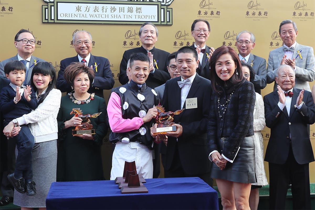 東方表行集團執行董事林慶麟伉儷(右)致送紀念品予「美麗傳承」的騎師梁家俊。
