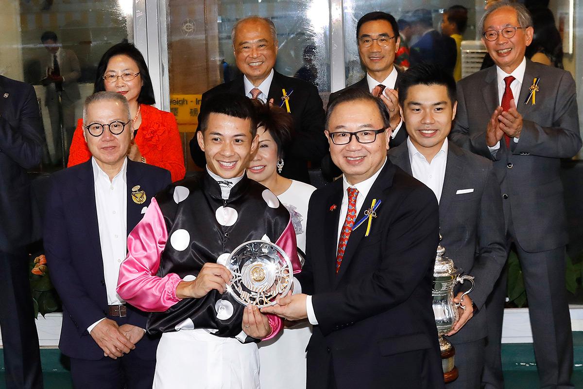 馬會董事廖長江(前排右一)於慶典盃頒獎禮上將冠軍獎盃及銀碟頒予「美麗傳承」的馬主郭浩泉及其家人、練馬師約翰摩亞及騎師梁家俊。