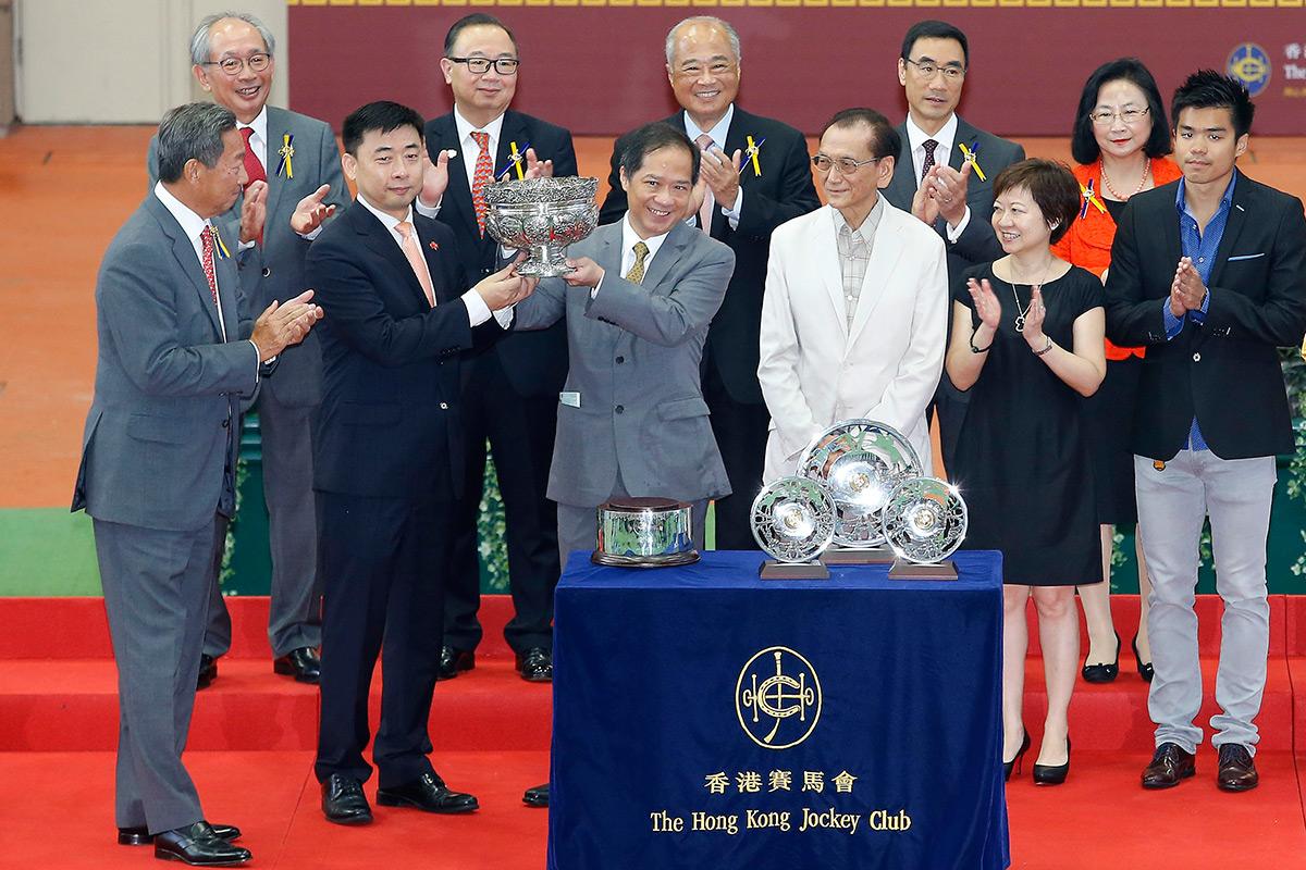 中央人民政府駐香港特別行政區聯絡辦公室宣傳文體部部長朱文(左),將國慶盃的獎盃頒發予勝出馬匹「飛來猛」的馬主代表。
