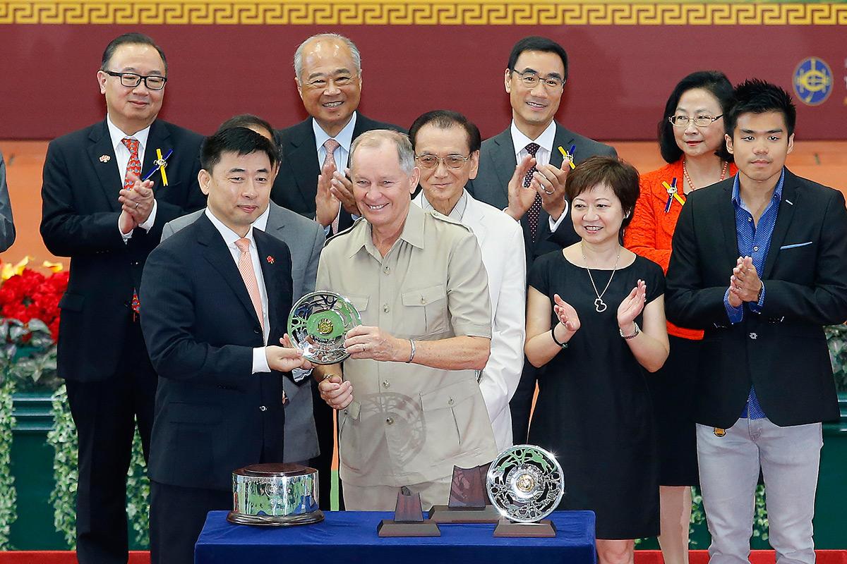 國慶盃頒獎儀式上,中央人民政府駐香港特別行政區聯絡辦公室宣傳文體部部長朱文(左)頒發銀碟予勝出馬匹「飛來猛」的練馬師約翰摩亞及騎師何澤堯。