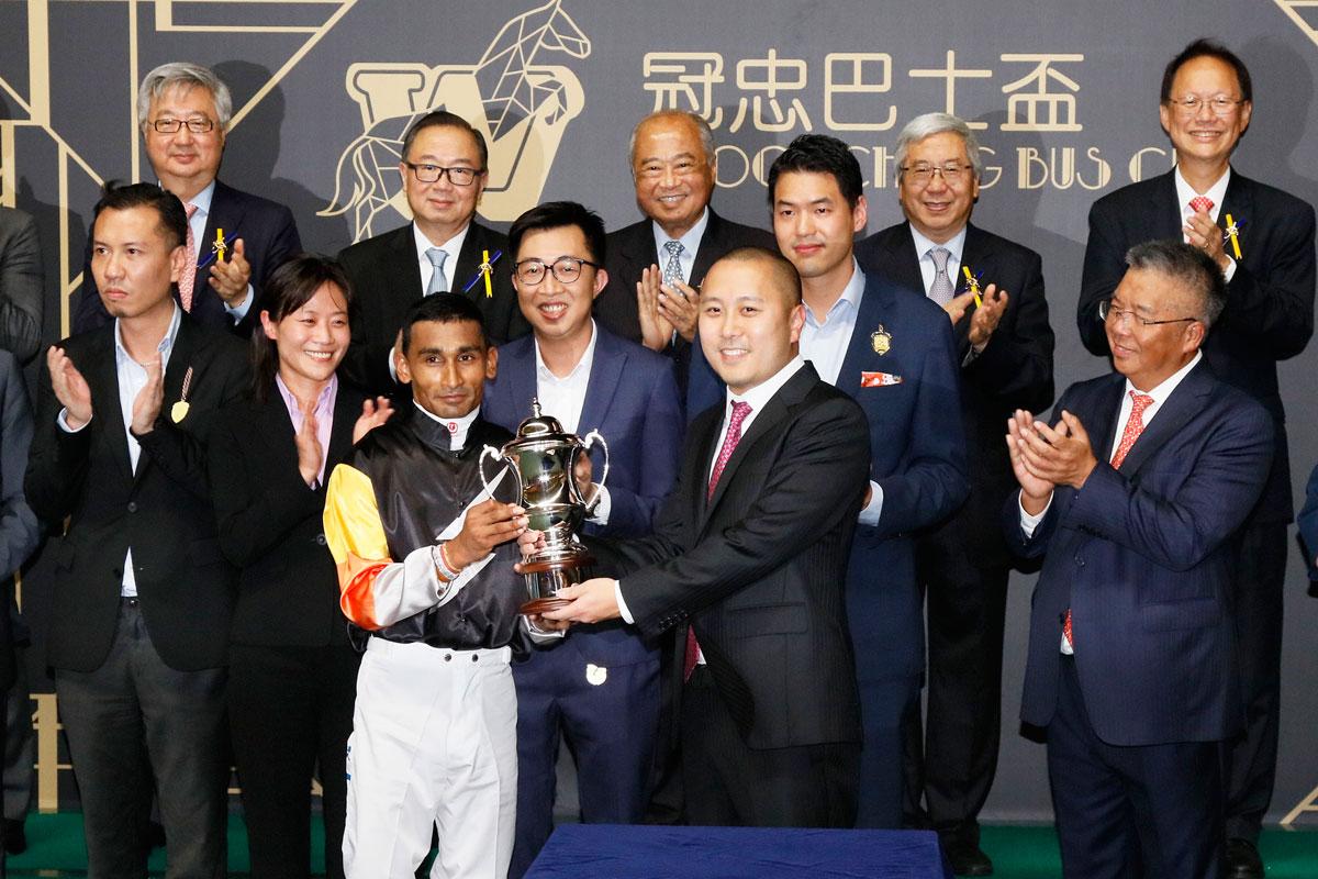 冠忠巴士集團有限公司執行董事盧文波頒發獎盃予「首映」的騎師田泰安。