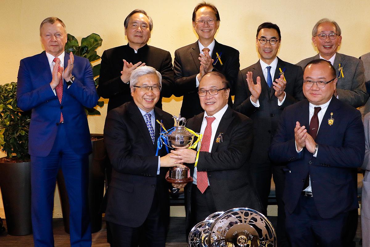馬會董事李家祥博士頒發一月盃獎盃予「鷹雄」的馬主蕭百君。