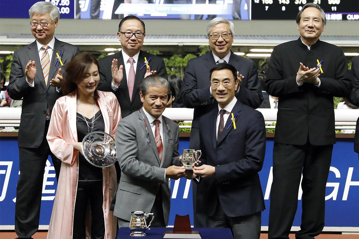 馬會董事利子厚(右)頒發跑馬地銀瓶及紀念品予「大雄圖」馬主潘蘇通的代表、練馬師告東尼,以及騎師沈拿。