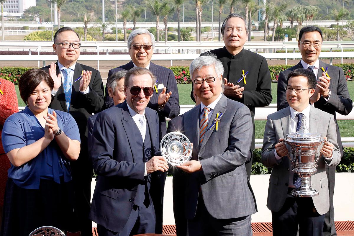 馬會董事楊紹信先生於頒獎禮上將短途錦標的冠軍獎盃及銀碟頒予「爭分奪秒」的馬主鍾韙㻺及親友、練馬師蔡約翰及騎師莫雷拉。