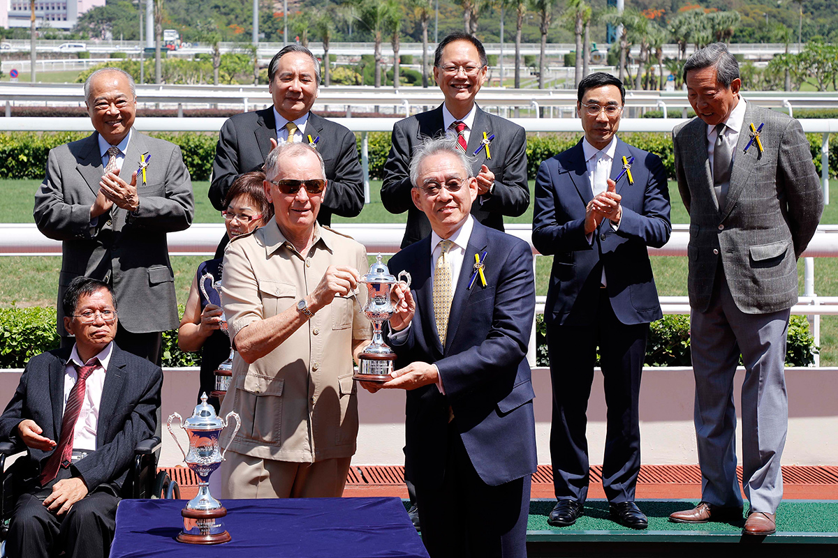 馬會副主席暨競駿會董事會主席周永健先生於頒獎禮上將獎盃及小型獎盃分別頒予「錶之太陽」的馬主代表、練馬師約翰摩亞及騎師潘頓。