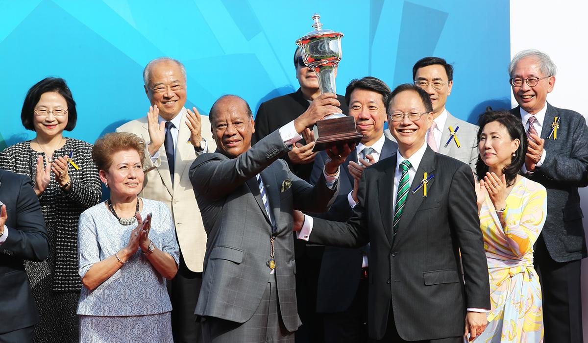 在渣打冠軍暨遮打盃頒獎禮上,馬會董事陳南祿頒發冠軍獎盃予頭馬「巴基之星」的馬主Kerm Din。