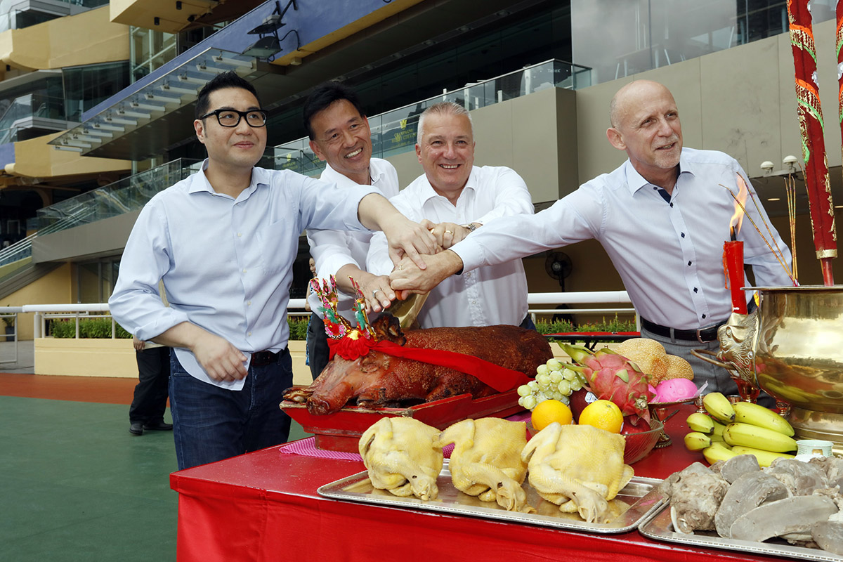 Senior Club officials carve the roasted pigs at the bai-sun ceremony.