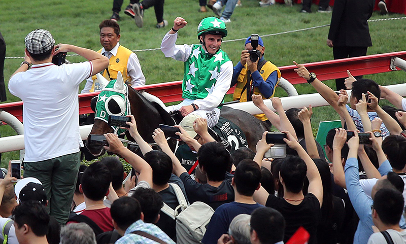 Jockey William Buick celebrates his success with the Sha Tin crowd after the race.