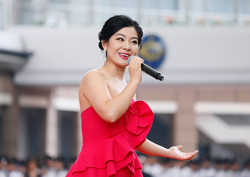 Cai Nan, a famous soprano from the China National Opera House, leads the national anthem accompanied by the Hong Kong Police Band.