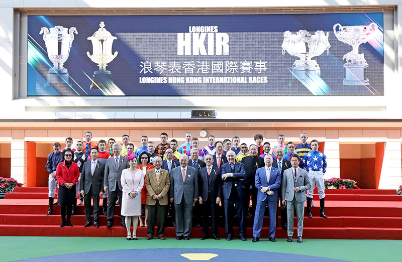 After Race 2, officiating guests, senior officials of the Club and all jockeys participating in the four Group 1 races greet racing fans in the Parade Ring to raise the curtain on this year's International Races. (first row from left) Ms. Karen Au Yeung, Vice President of LONGINES Hong Kong; Mr. Lester C H Kwok, Deputy Chairman of HKJC; The Honourable Geoffrey Ma Tao-li, The Chief Justice of the Court of Final Appeal of the Hong Kong Special Administrative Region Dr. Anthony W K Chow, Chairman of HKJC; Mr. Walter von Känel, President of LONGINES, Mr. Winfried Engelbrecht-Bresges, Chief Executive Officer of HKJC; Mr. Aaron Kwok, LONGINES Ambassador of Elegance