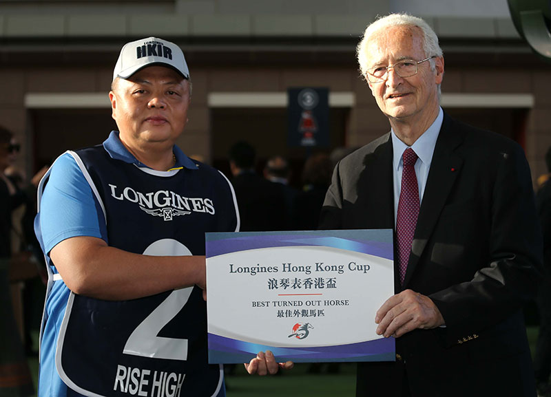Mr Louis Romanet(right), Chairman of the International Federation of Horseracing Authorities, presents a cheque of HK$5,000 to the groom responsible for Rise High, the Best Turned Out Horse in the LONGINES Hong Kong Cup.