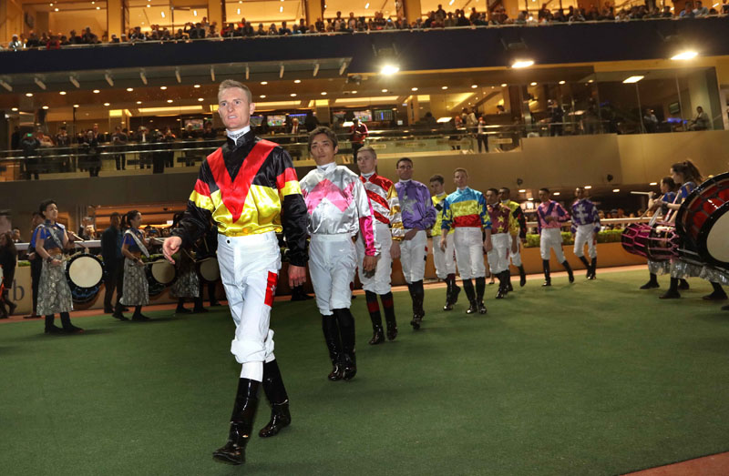 Jockeys enter the turf track in front of the crowd.