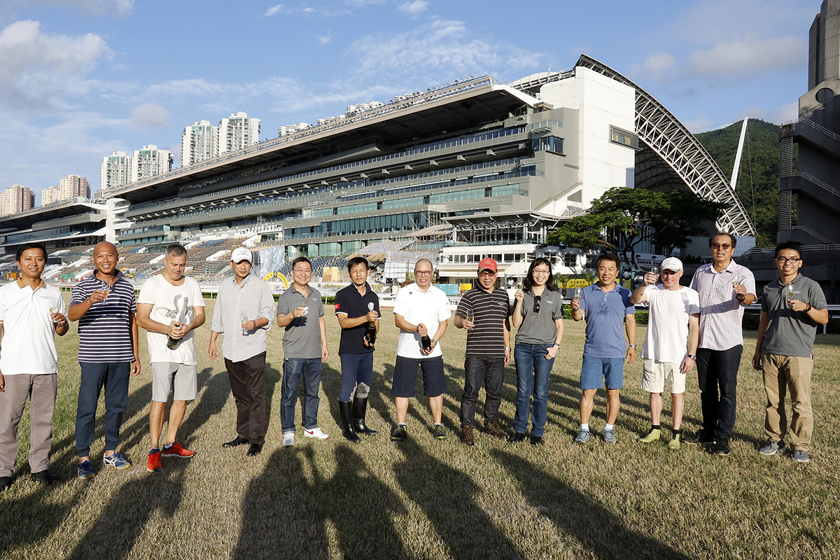 Club officials and trainers join the champagne toast at Sha Tin Racecourse.