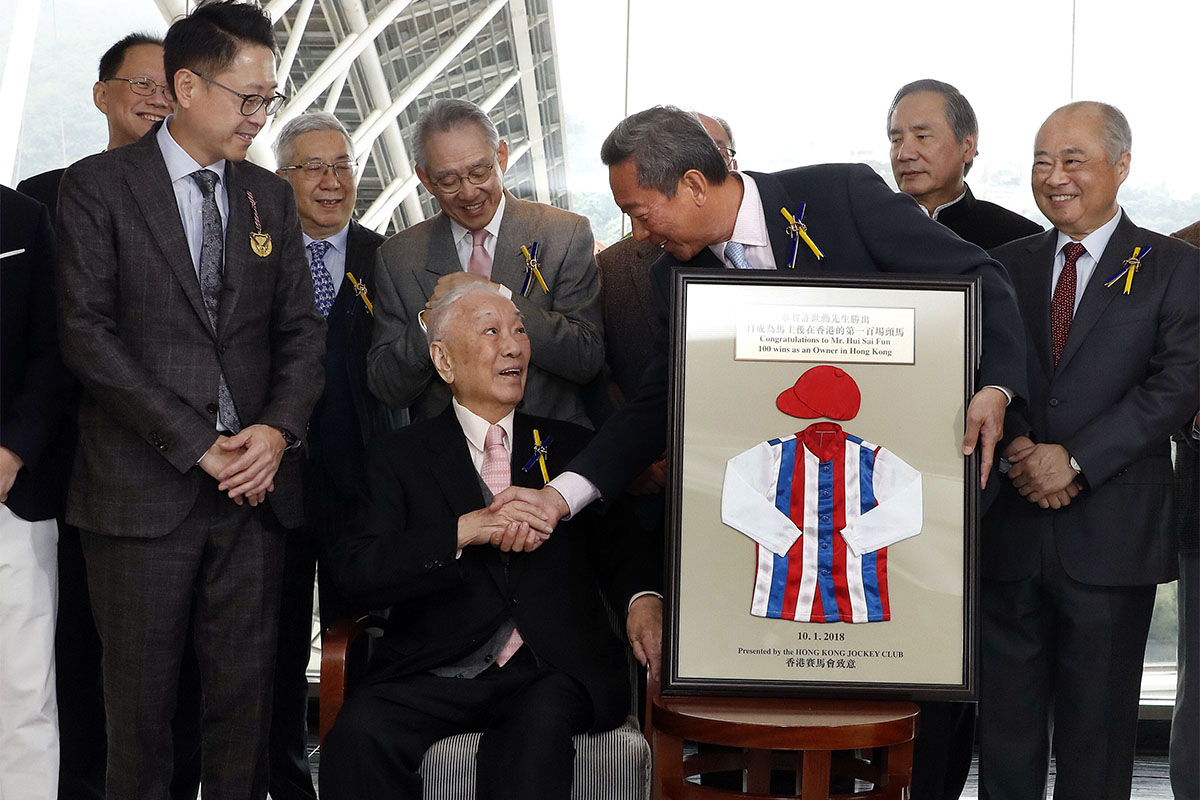 Club Chairman Dr Simon Ip (front row, first from right) presents a souvenir frame and commemorative DVD to Mr Hui Sai Fun in a ceremony held at Sha Tin Racecourse today.