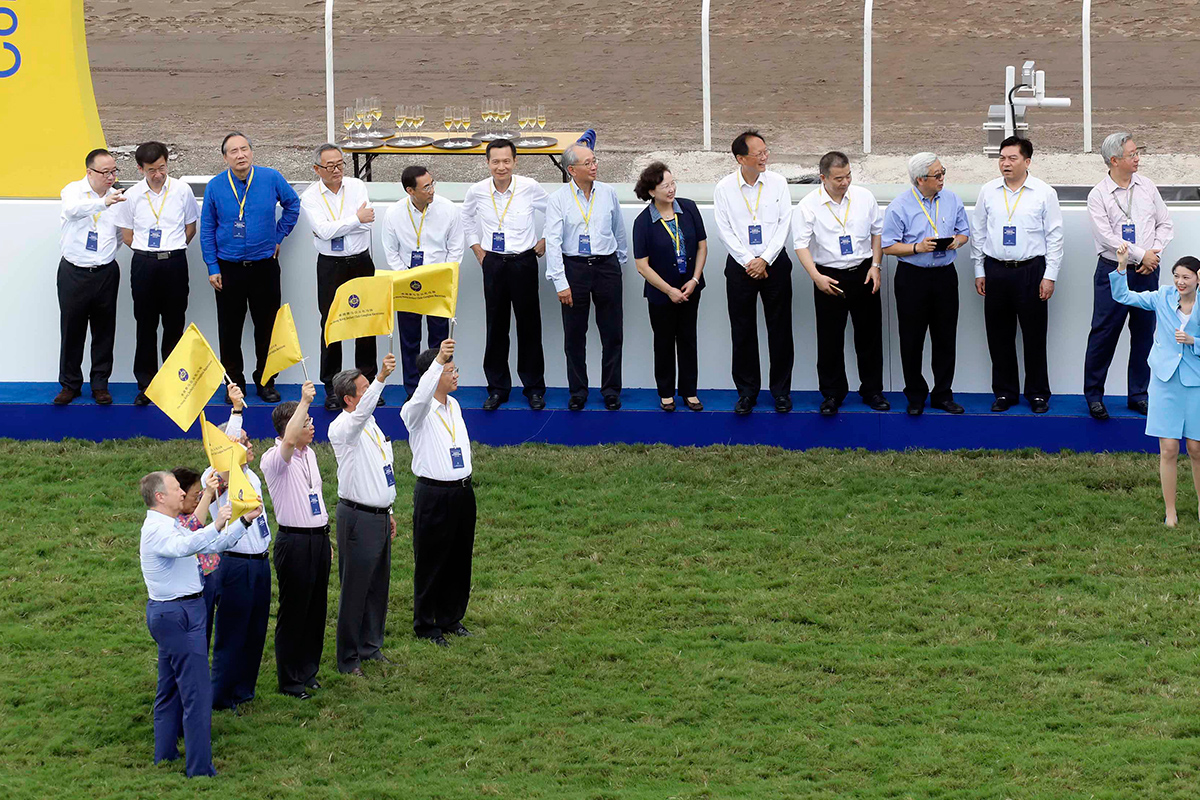 Officiating guests raise commemorative flags to start the horse jump-out as a highlight of the opening ceremony.