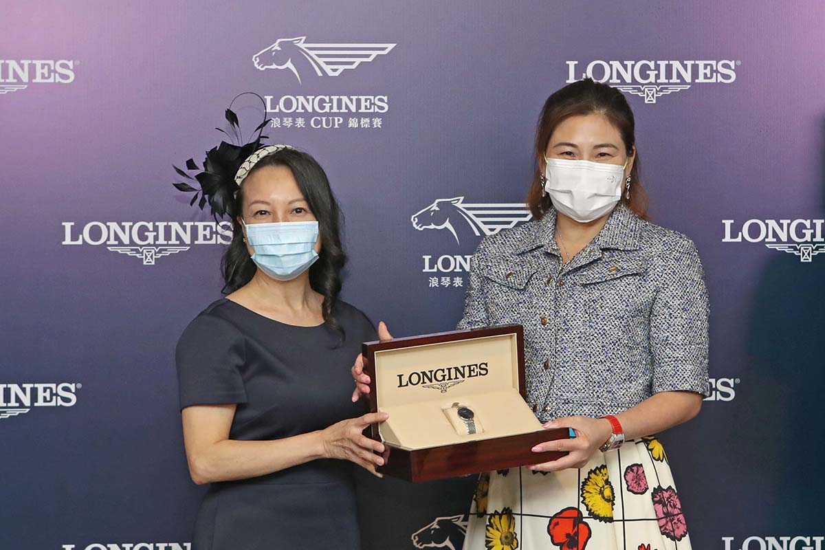 Ms. Nancy Tse, Vice President of LONGINES Hong Kong, presents a LONGINES Master Collection watch to the owner representative of Beauty And The Best Syndicate, trainer Douglas Whyte and jockey Keith Yeung, winning connections of Best Alliance.